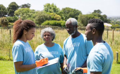volunteers standing in a field wearing gloves